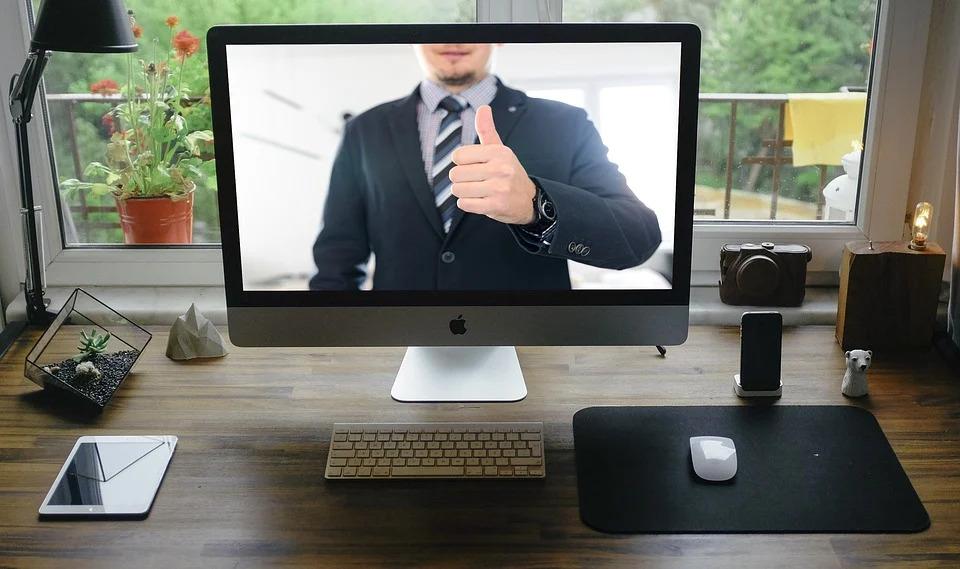 """Computerbildschirm mit Person im Anzug und dem """"Daumen hoch""""-Zeichen"""